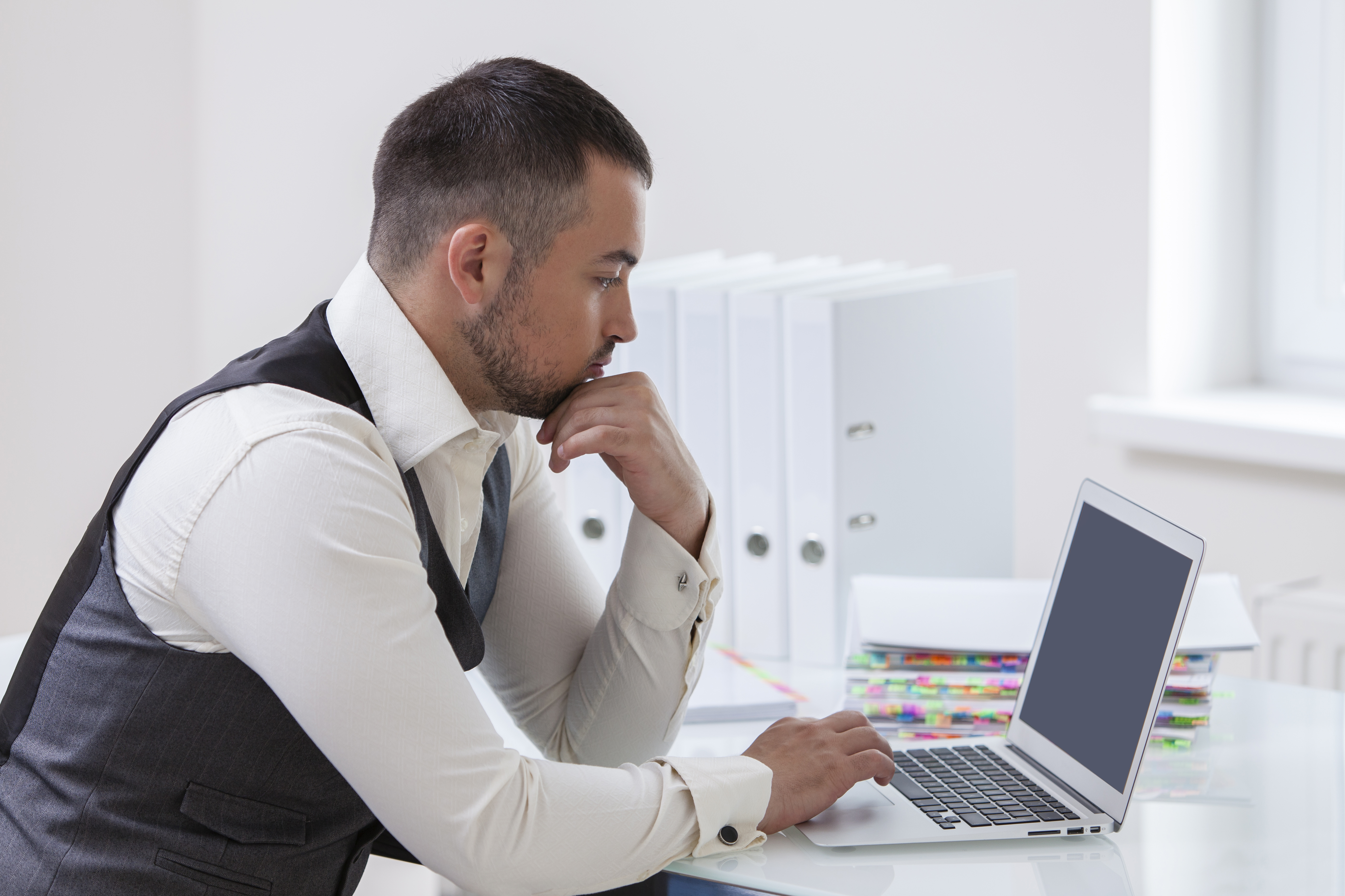 Office ergonomics could help this man who is hunched over a laptop.