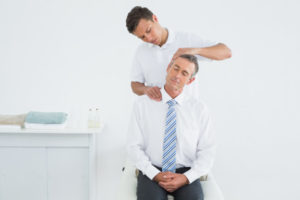 A chiropractor providing onsite care to an office office worker