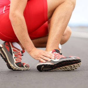 Broken twisted angle - running sport injury. Male runner touching foot in pain due to sprained ankle.